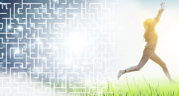 woman running happily through field having escaped a maze